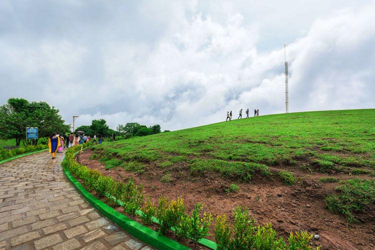 People on footpath amidst field against sky