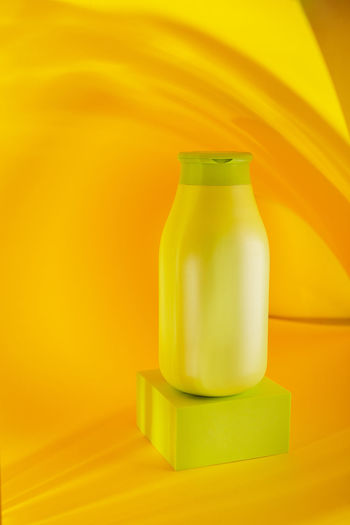 Close-up of yellow bottle on table against wall