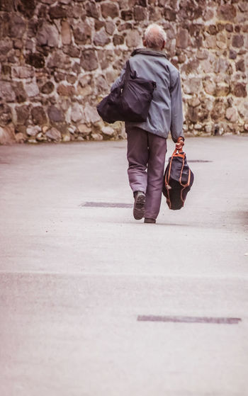 Full Length Walking One Person Real People Rear View Men Day Lifestyles City Street Bag Luggage Outdoors Adult Footpath Leisure Activity Wall Casual Clothing Walking Cane Leather Man Leaving Going Away Going Somewhere Traveling Baggage Senior Adult Alone Loneliness