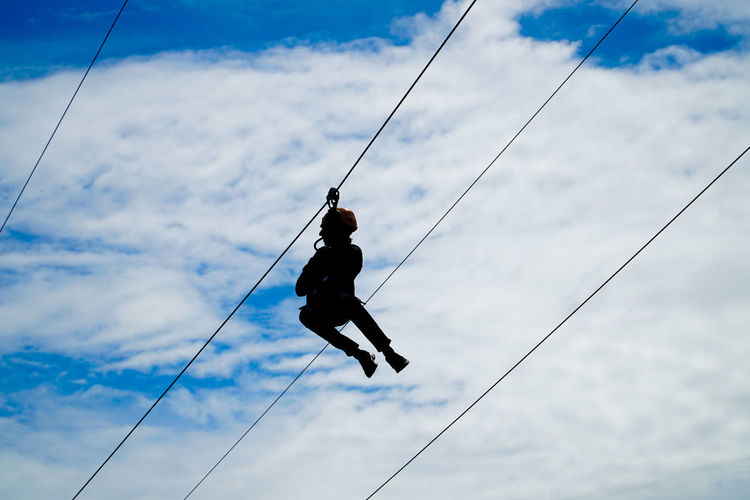 Low angle view of man hanging on cable against sky