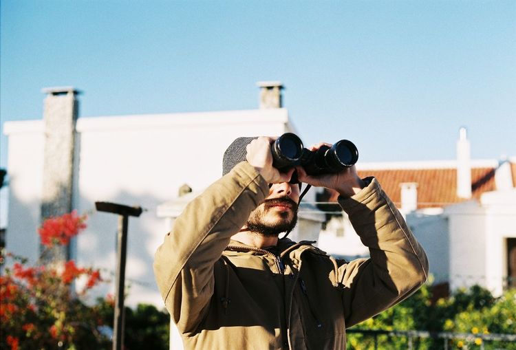 Man Using Binoculars While Standing Against Building