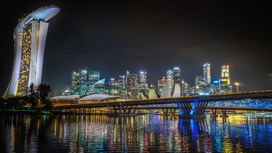 Illuminated Marina Bay Sands By River Against Sky At Night