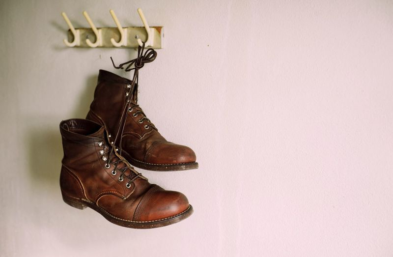 Leather shoes hanging on the wall Vintage Shoe Indoors  Wall - Building Feature No People Pair Copy Space Fashion Leather Boot Brown Close-up Still Life Text Clothing