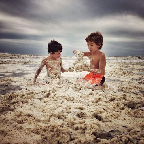 Siblings playing on beach against sky
