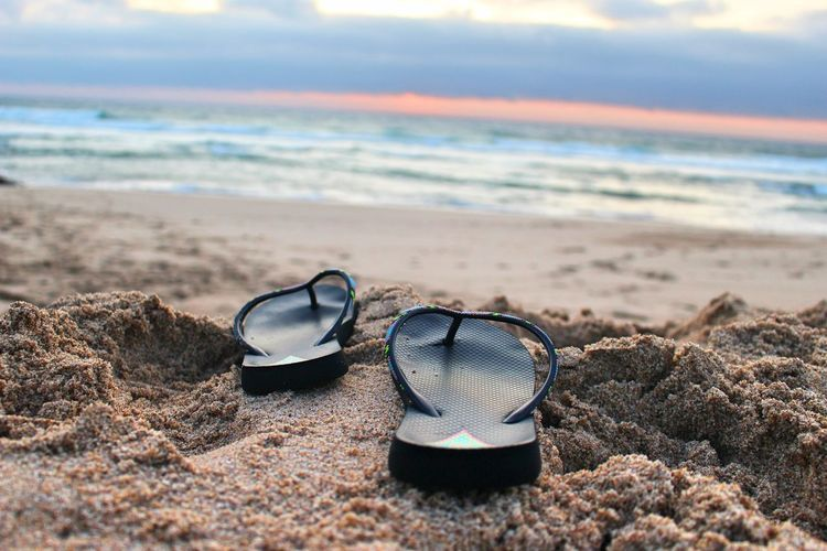 Close-up of sunglasses on sand at beach against sky