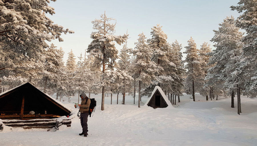 A male traveler reads a map in front of a wooden shelter in a snowy winter forest in Lapland Hiking Lapland Travel Advanture Beauty In Nature Cold Temperature Day Field Hiker Leisure Activity Lifestyles Nature Outdoors Plant Real People Sky Snow Snowcapped Mountain Snowy Snowy Forest Traveler Tree Winter Winter Activities Winter Forest