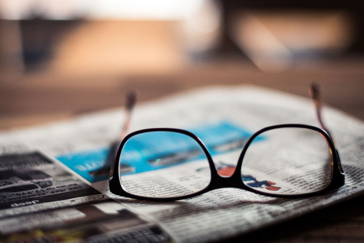 Close-Up Of Eyeglasses On Newspaper At Table
