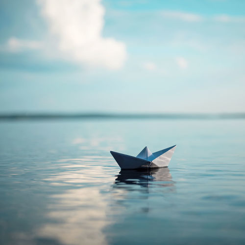 Paper boat floating on sea