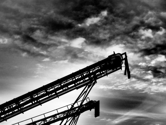 Low angle view of cranes against cloudy sky