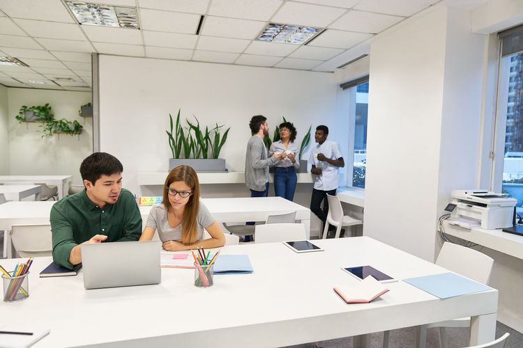 View of cheerful colleagues working in office