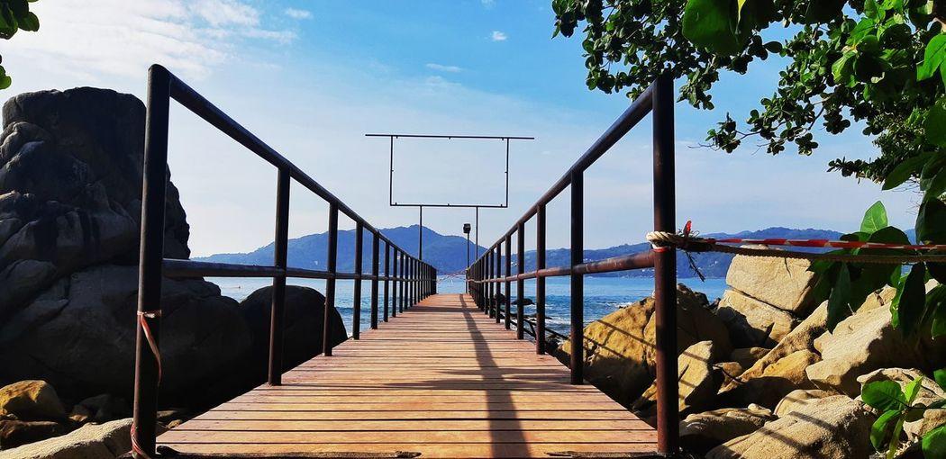 Footbridge over pier against sky