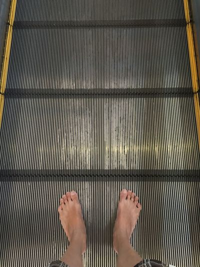 Low section of woman on escalator