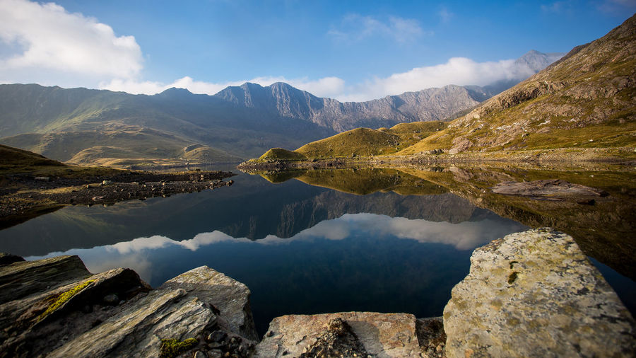 Beautiful mountainscape in north Wales Reflection United Kingdom Wales Blue Sky Clouds Foreground Idyllic Lake Lake View Landscape Mountain Mountain Range Mountains Mountainscape Nature Outdoors Peak Remote Scenics - Nature Sky Snowdonia National Park Stones Tranquil Scene Water Wideangle