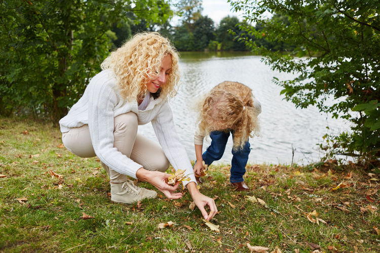 Girl with mother collecting autumn leaves on field by lake