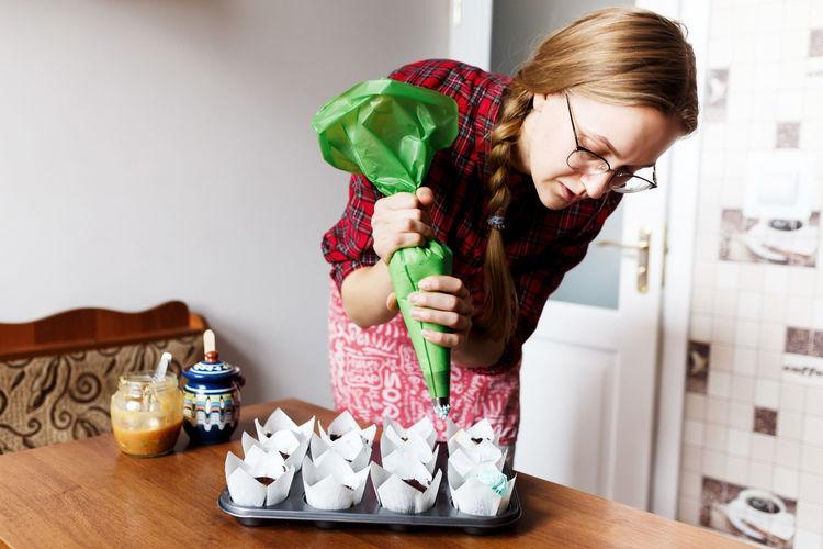 Full length of girl holding ice cream standing on table