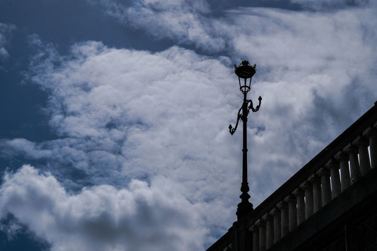 Low angle view of street light and building against sky