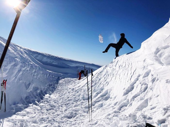 Low Angle View Of Man Kicking Snow Against Blue Sky During Sunny Day