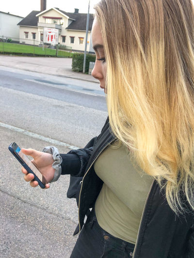 Midsection of woman holding smart phone while standing on road
