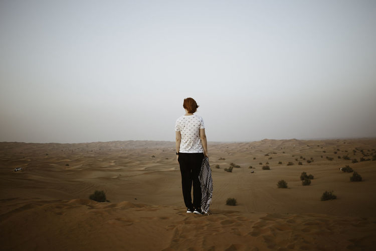Rear view of woman standing on sand in desert