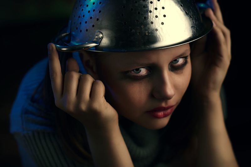 Close-up portrait of serious teenage girl with colander against black background
