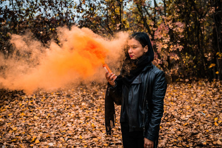 Young woman holding distress flare while standing in forest during autumn