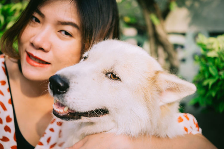 Close-up portrait of smiling woman holding dog