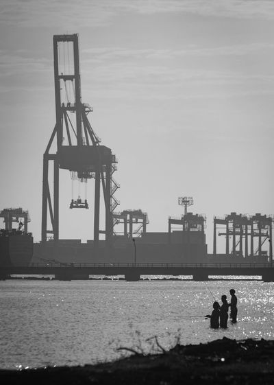 Silhouette people fishing in sea against construction site