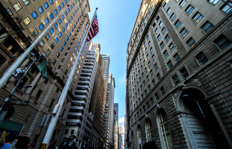 Low angle view of american flag amid buildings against clear sky