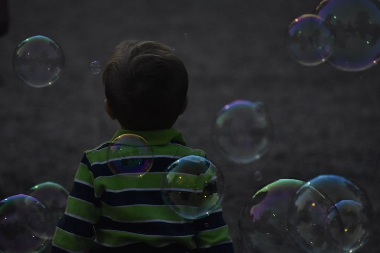 Rear view of boy standing amidst bubbles