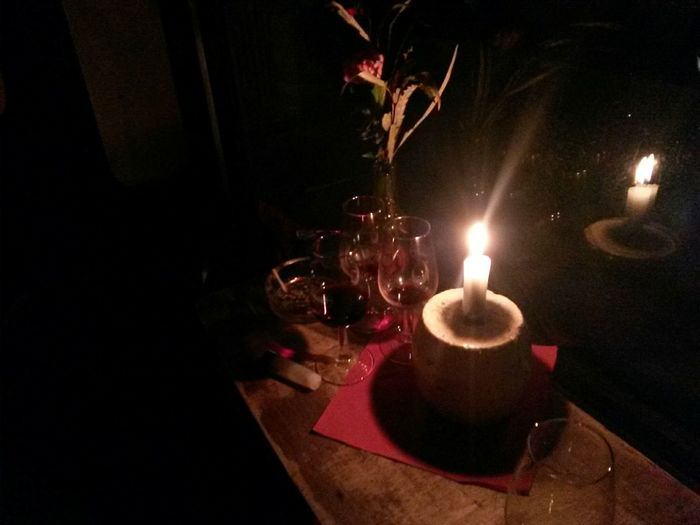 View of lit candle in dark room