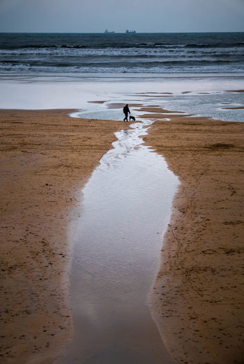 Man standing on beach by sea against sky