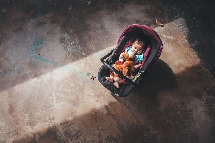 High angle view of toddler with toy in baby carriage outdoors