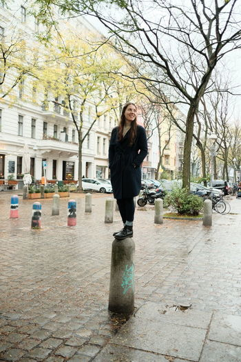 Portrait of young woman standing on footpath in city