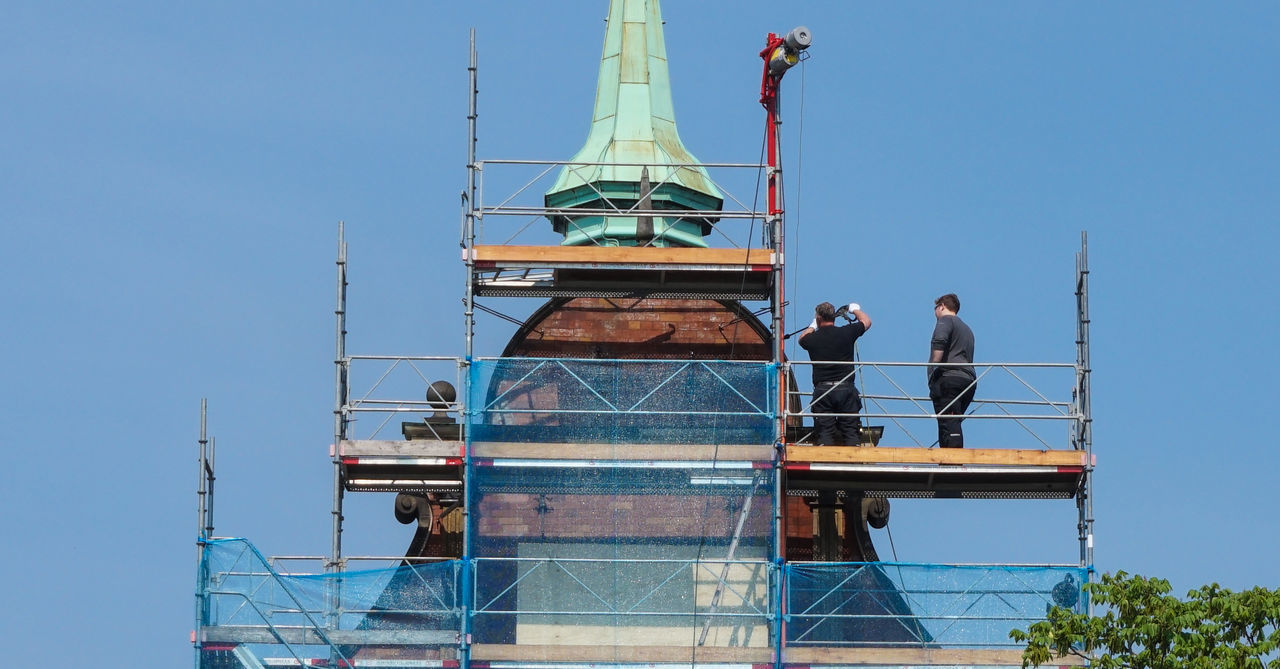 Low Angle View Of Men Working Against Clear Blue Sky