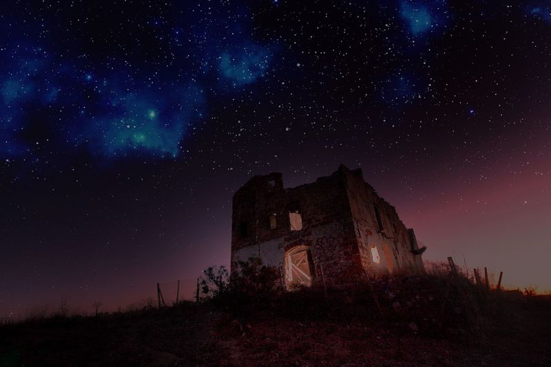 Low angle view of abandoned house against sky at night