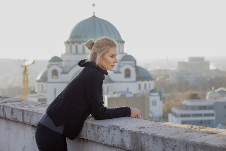 Thoughtful woman leaning on retaining wall against church of saint sava