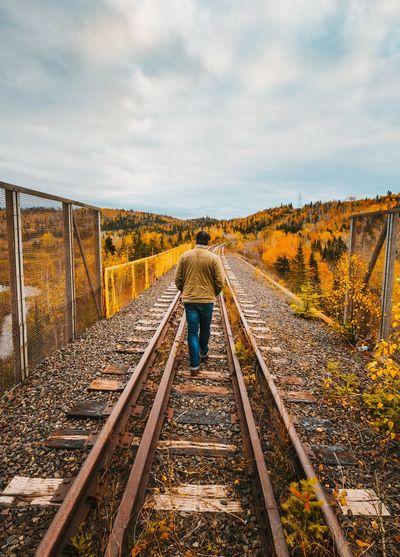Rear view of person standing on railroad tracks against sky