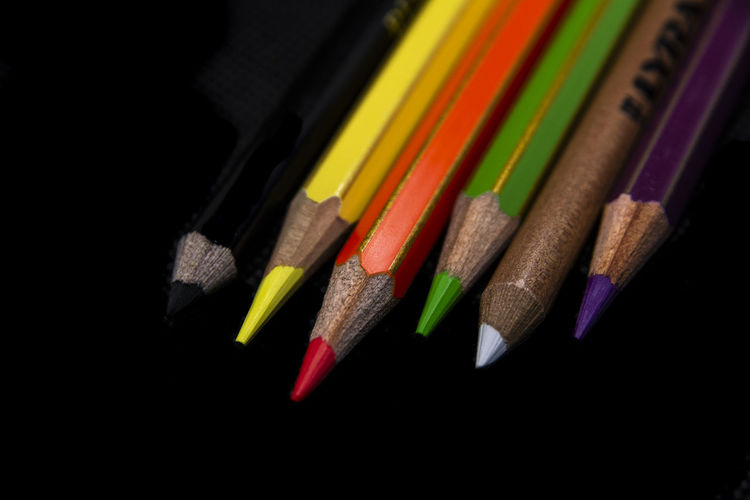 High angle view of colored pencils on black background