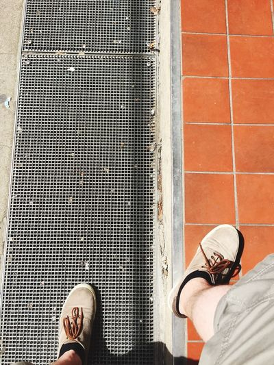 Low Section Of Man Standing On Sewage Metal Grate And Sidewalk