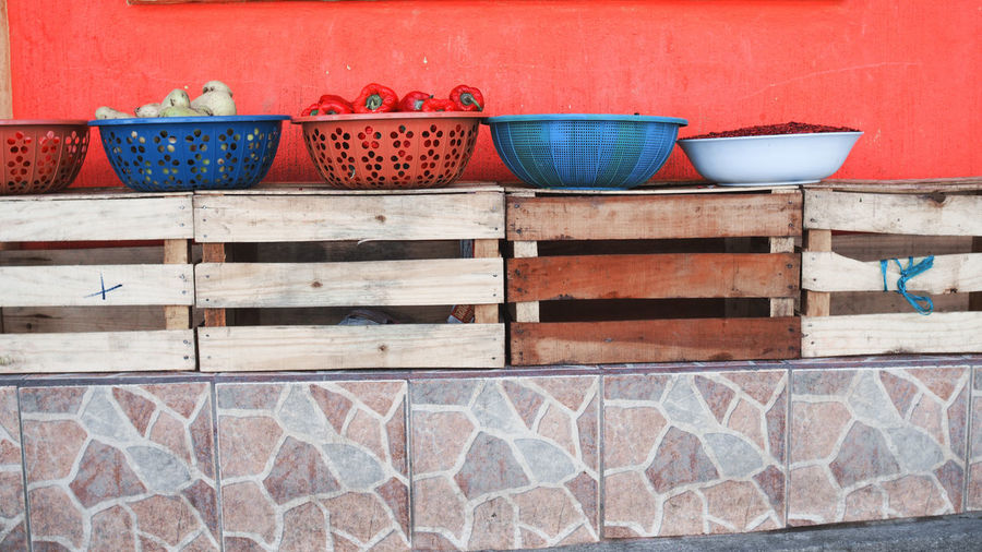 Containers on wooden crates against wall
