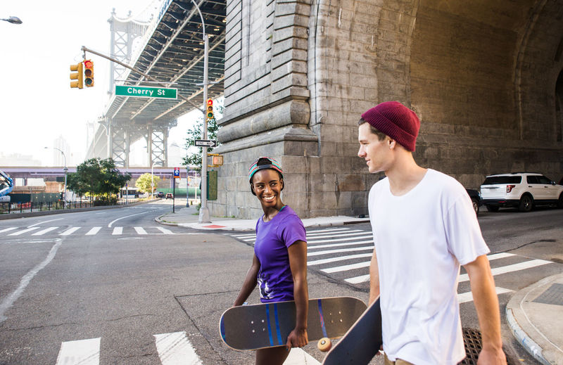 Young man with woman walking on road while holding skateboard