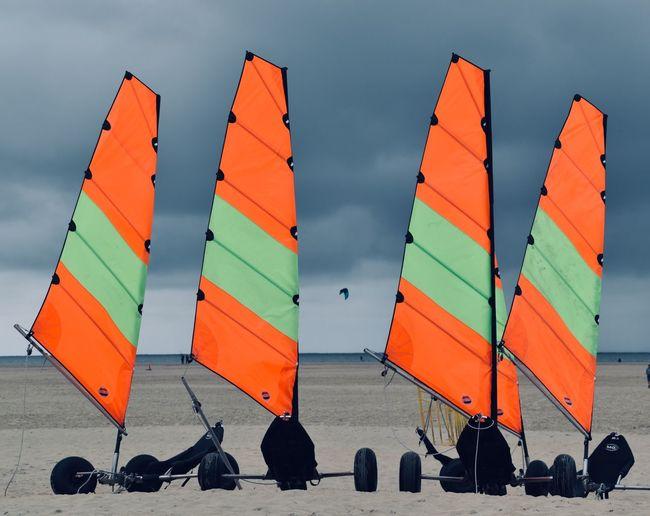 Windsurfs at sandy beach against cloudy sky