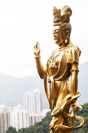 Goddess statue overlooking the city of Hong Kong at the Temple of 10,000 Buddhas. Buddha Hong Kong Temple Of 10,000 Buddhas Architecture Art And Craft Belief Buddhist Temple Buddism Buddist Temple Built Structure Creativity Day Goddess Gold Colored Human Representation Male Likeness Nature Religion Representation Sculpture Sky Spirituality Statue