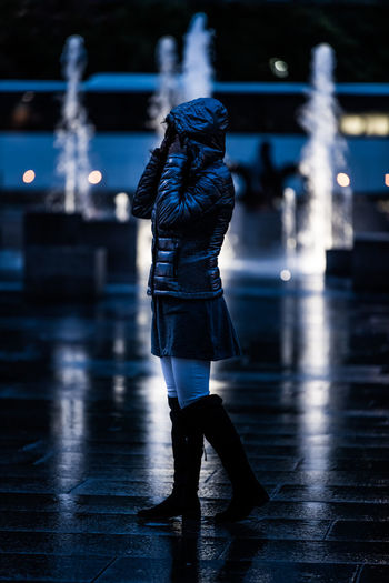 Woman wearing jacket standing against fountain