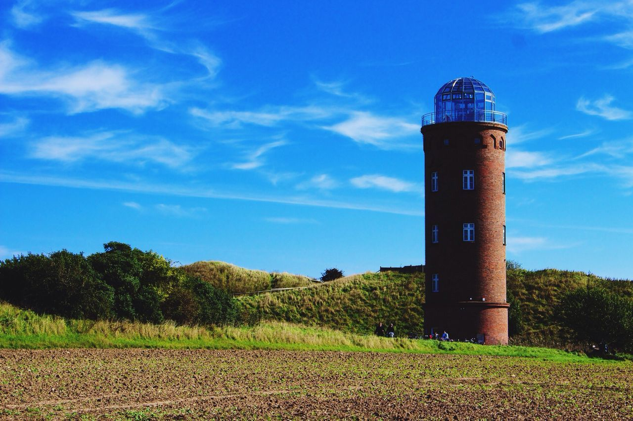 Lighthouse On Grassy Field By Trees Against Sky