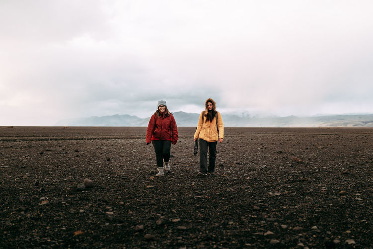 Rear view of women standing on land against sky
