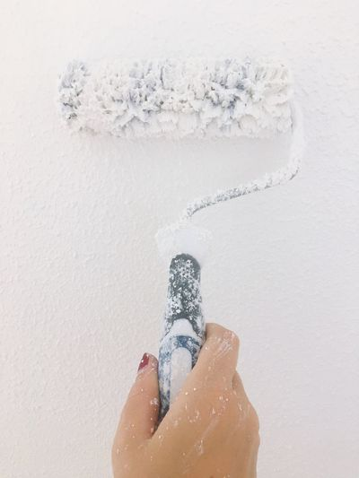 Close-up of woman painting wall with paint roller
