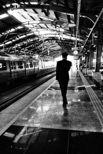 Rear view of man standing on railroad station platform