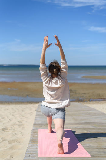 Rear view of woman doing yoga on beach