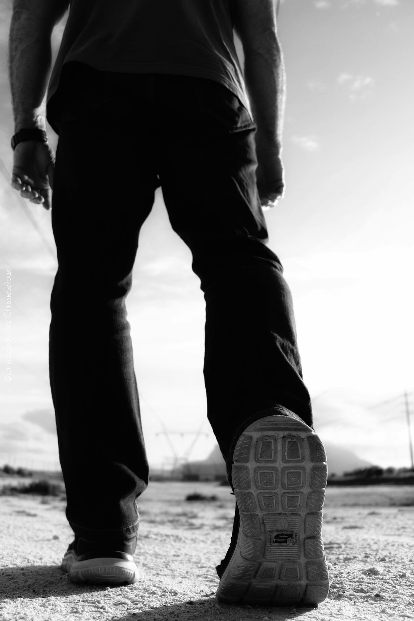low section, one person, human leg, body part, real people, lifestyles, human body part, men, shoe, sky, day, standing, nature, focus on foreground, leisure activity, casual clothing, outdoors, sunlight, land, jeans, human limb, human foot